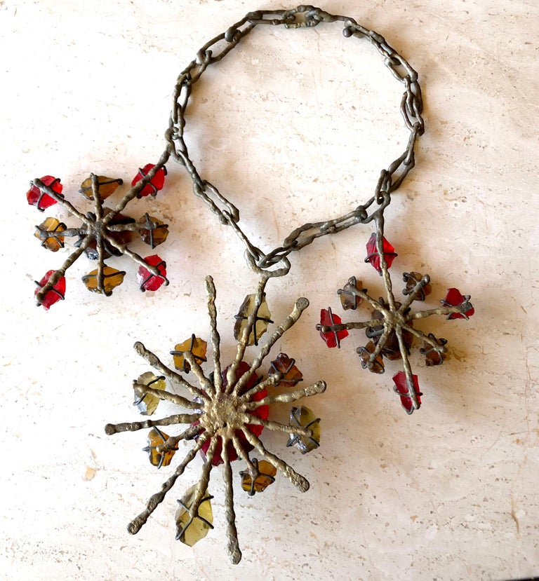 Brutalist metal sculpture necklace created by Jack Hoag of Orinda, California circa 1970's.  Necklace is reminiscent of the work of Claire Falkenstein and is comprised of three large metal pendants which contain rough cut glass parts and hang from a