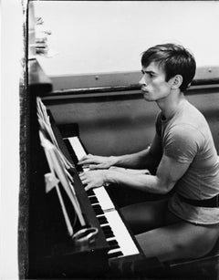 Rudolf Nureyev photographed playing the piano during a rehearsal break
