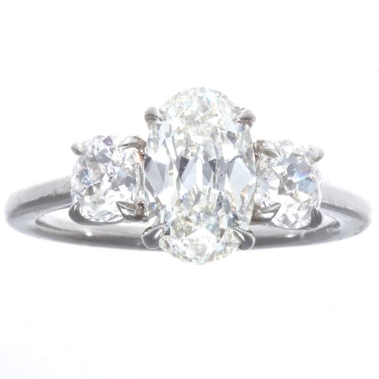 Hard to believe the center stone weighs only 1.64 carats. The oval brilliant cut is unique and full of life. GIA certified J color, VVS1 clarity.  Accented by two old mine cut diamonds weighing  approximately  0.70 carats, G-H color SI clarity. The