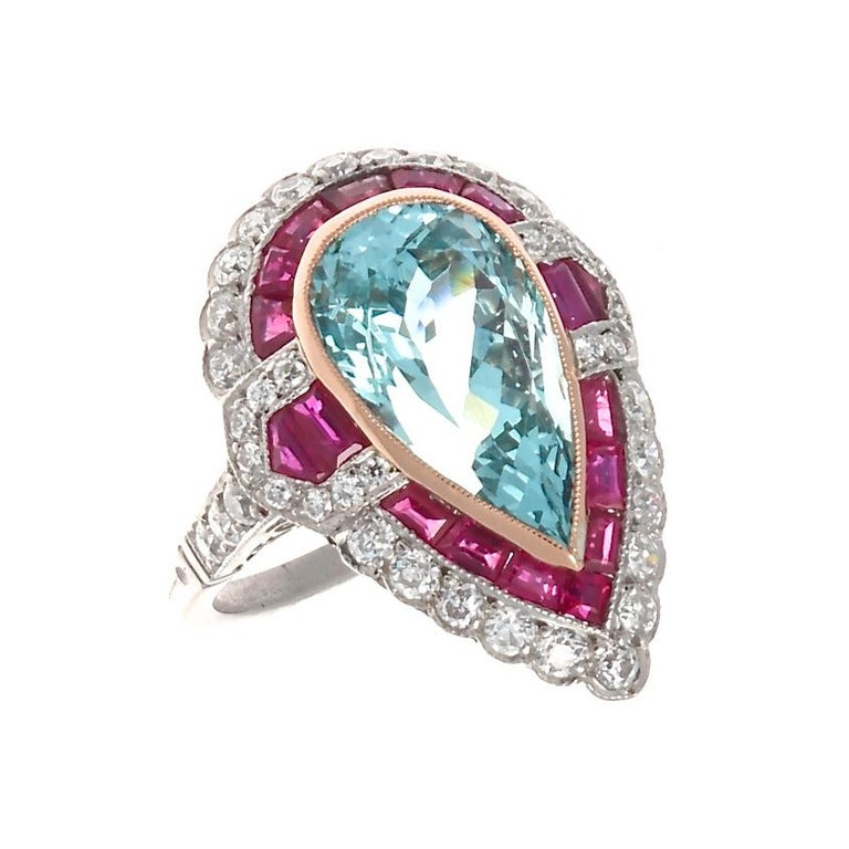 A symphony of color and geometric balance that is exemplary of the fantastically stylish art deco era. Featuring a glowing 6 carat pear shaped aquamarine surrounded by expertly calibrated vibrant red rubies and perfectly complimented by colorless
