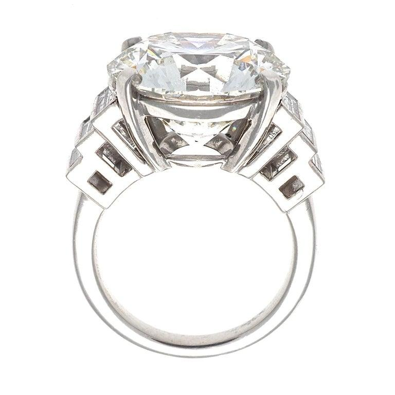Featuring a 12.23 carat round brilliant cut diamond that is GIA certified as J color, VS2 clarity, triple X. Excellently cut to perfection for maximum beauty and sparkle. Set among descending near colorless baguette cut diamonds. Crafted in