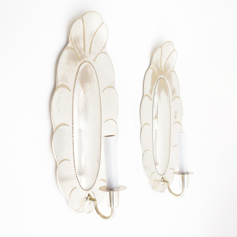 Large pair of Swedish art deco silver plated sconces from Jacob Ängman for GAB, Stockholm. The sconces have been newly polished, lacquered and electrified with candelabra sockets. Light wear to backplates with silver loss.   Measures: Height 15