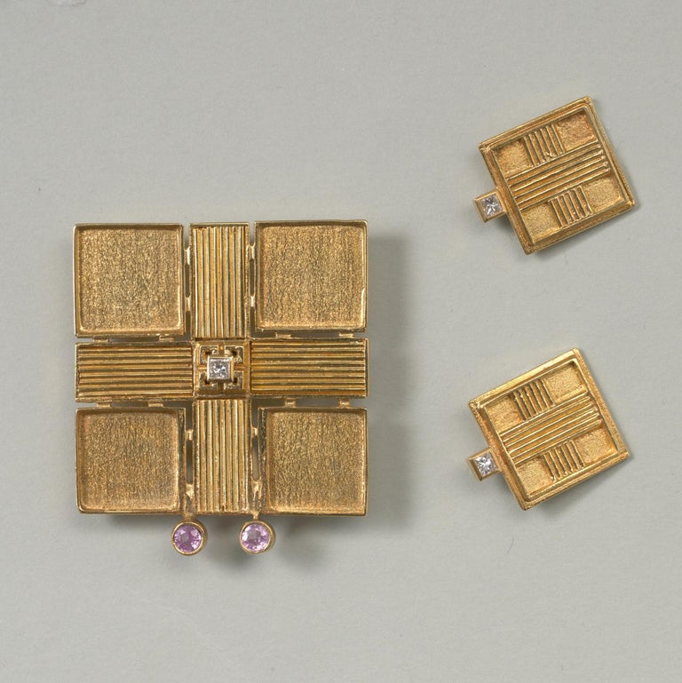 A square 18 carat gold brooch with a triped cross and a square cut diamond at the center, at the bottom of the brooch are two brilliant cut pink tourmalines, Jacob de Groes, Netherlands.  weight: 21.3 grams dimensions: 4.3 x 3.7 cm  A pair of