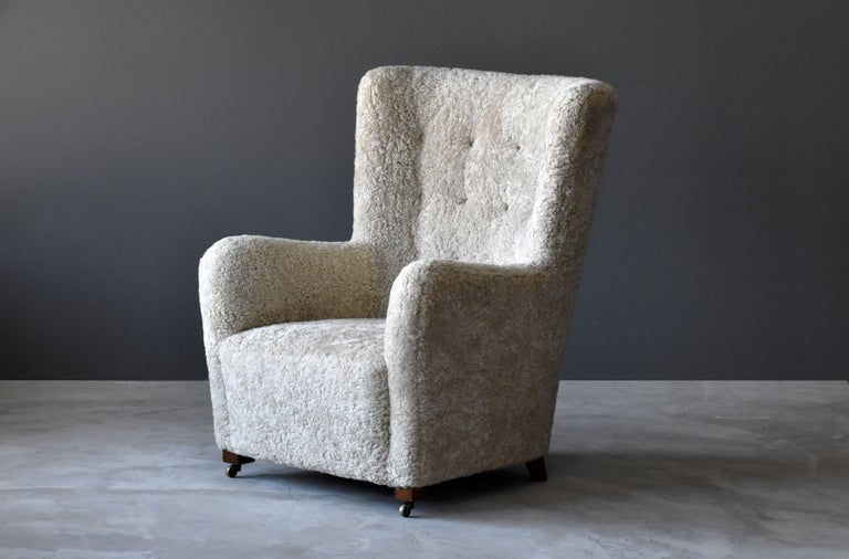 An early modernist lounge chair, design, and production attributed to modernist cabinet maker, Jacob Kjær. Produced in Denmark, 1940s. Overstuffed organic form rests on stained beech legs with front legs brass castors mounted.  For further