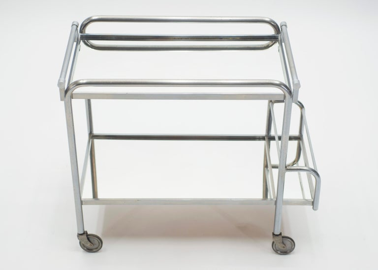 This chic bar cart from the 1930s carries with it the elegant mood of the Art Deco period, especially with its bold, modern use of high-quality metals and mirror. It's set on functioning wheels and has 2/3 mirrored surfaces on which to store your