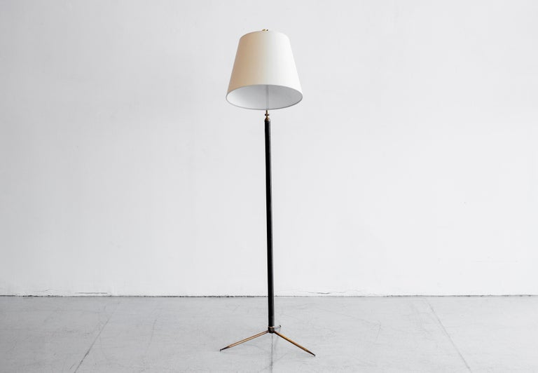 French floor lamp attributed to Jacques Adnet. Brass stem wrapped in rich dark brown leather with contrast stitching and brass tripod base. Newly re-wired with new shade.