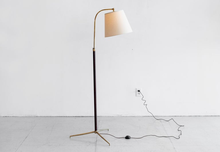Handsome French floor lamp attributed to Jacques Adnet. Stem wrapped in dark red-brown leather with contrast stitching and brass tripod base. Arched brass neck adjusts in height from 50