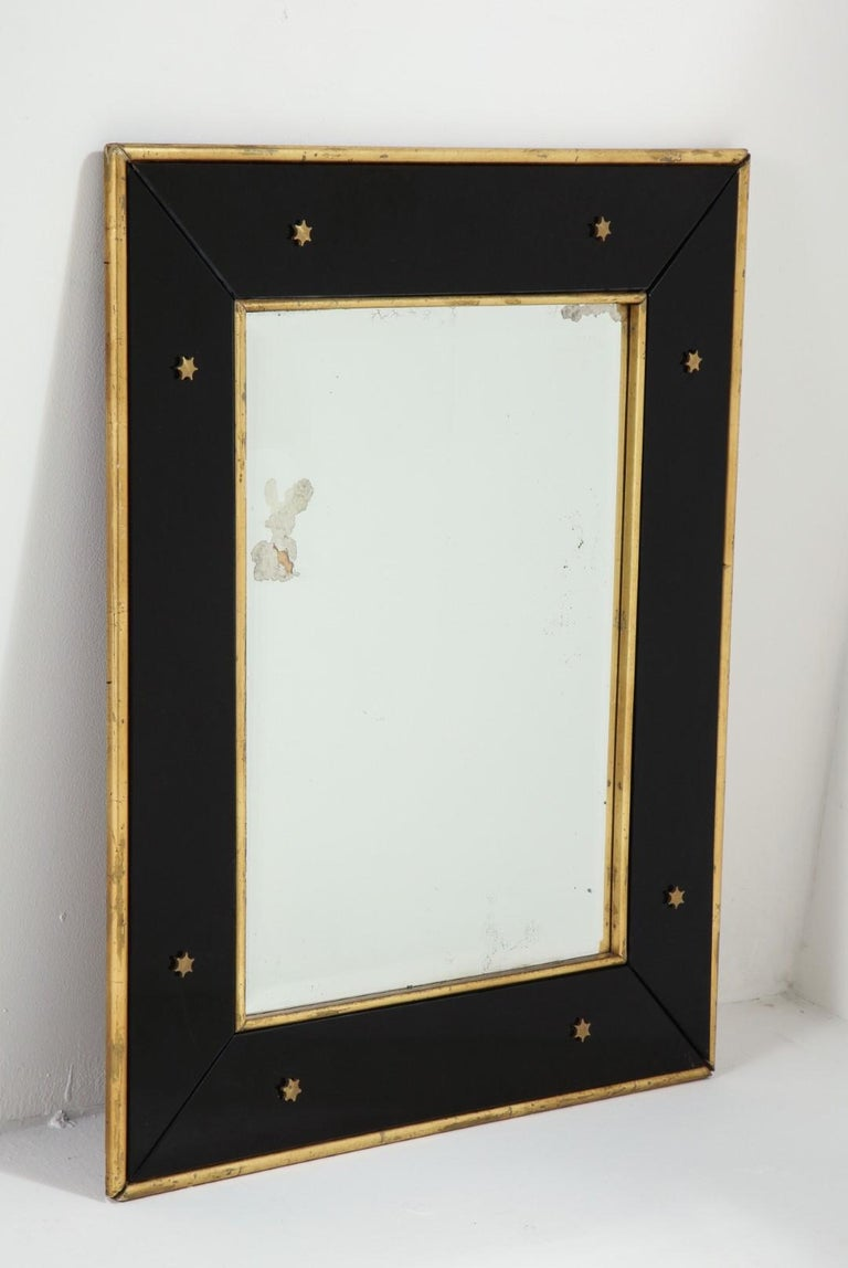 Wall mirror by Jacques Adnet, circa 1940. Black glass frame with gold leaf border and star detail on the glass.