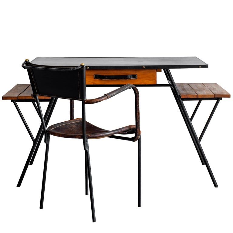 Rare Jacques Adnet desk and armchair. Desk has black leather top, oak wood drawer with leather handle, two oak open side shelves and black lacquered metal legs. Chair has great two-tone leather with a saddle brown seat and arms showing fantastic age
