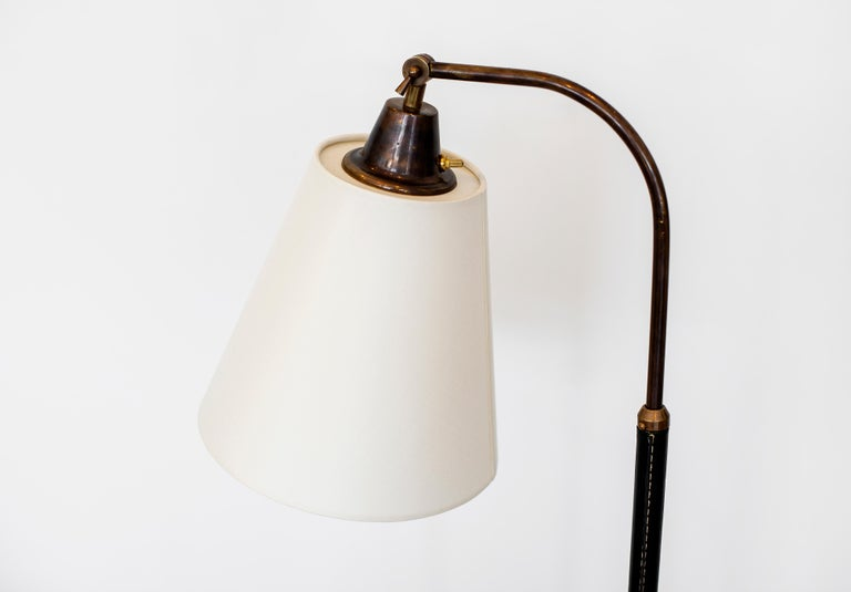 Fantastic French floor lamp with hand-stitched black leather, black metal conical base and height adjustable brass neck. Newly rewired with new silk shade that pivots.