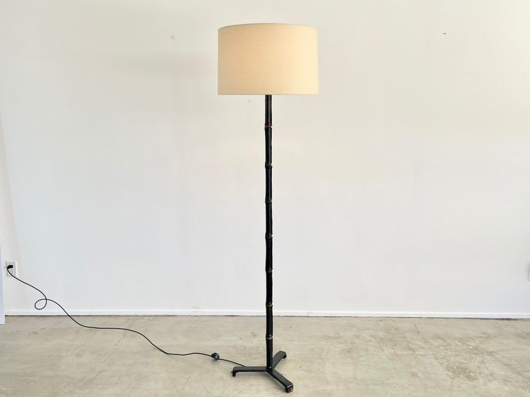 Incredible leather wrapped floor lamp with signature bamboo leather and brass stem and contrast stitching. Leather all the way down to the tripod base.  Newly rewired with new silk shade.
