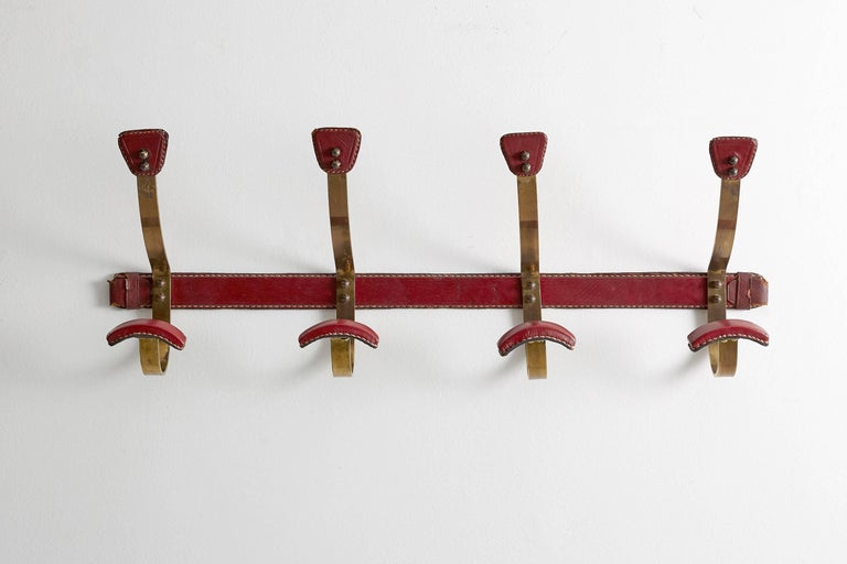 Rich red leather wrapped brass coat rack with signature Adnet leather and contrast stitching.