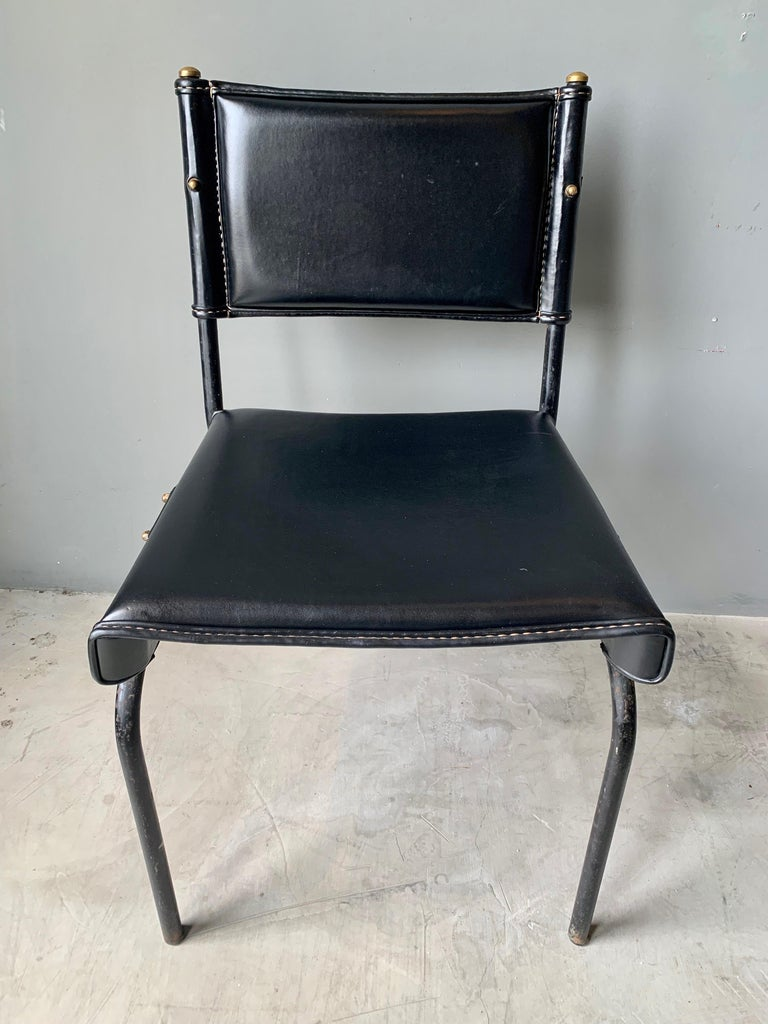 Stunning chair and footstool by French designer Jacques Adnet. Iron frame with black leather throughout. Original leather in very good condition. Signature Adnet contrast stitching. Gorgeous set.   Chair dimensions: 31.5