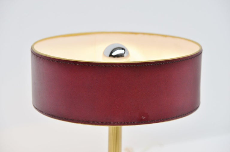Very nice and highly decorative table lamp designed by Jacques Adnet, France, 1960. This leather clad table lamp has a square shade and a brass stem, the shade is made of leather too. High quality stitching on this lamp. The lamp is in very nice