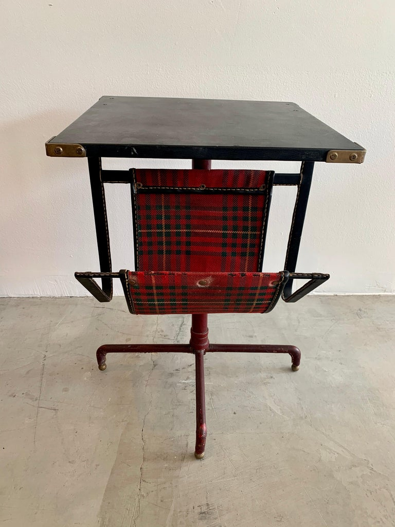 Very unusual side table by Jacques Adnet. Completely wrapped in leather. Tabletop is black leather with brass corners. Frame is also wrapped in black leather and extends down, holding a plaid and leather shelf for holding books or magazines. Base is