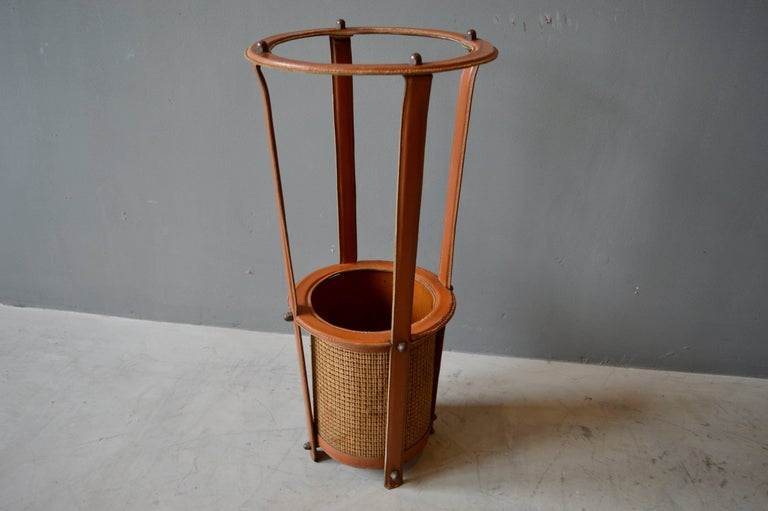 Rare umbrella stand by Jacques Adnet. Saddle leather wrapped frame with brass hardware and caning. Signature Adnet contrast stitching. Great vintage condition.