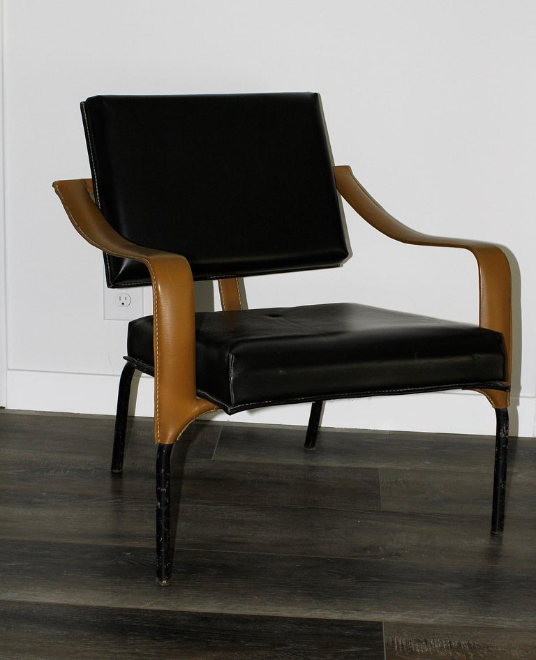 """Extremely rare pair of lounge chairs by Jacques Adnet. Original condition. France, circa 1955-1960. Edited by Mercier Freres, Paris 12. Black and brown faux leather on black lacquered metal Measurements: Height 29"""", height2 15""""1/2, width 25""""3/4,"""