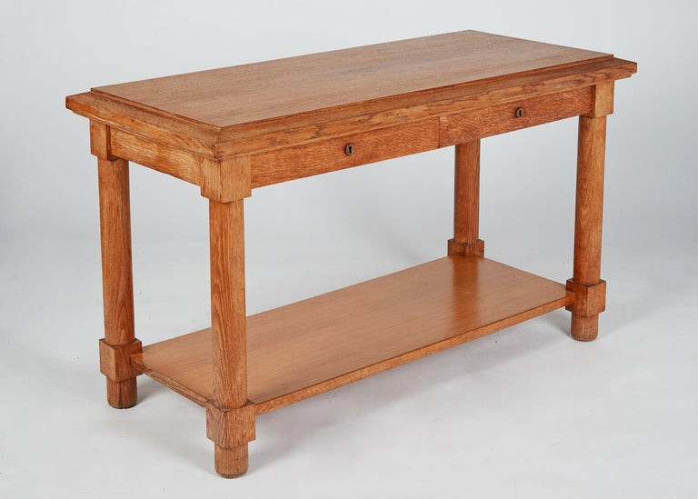 By famed French designer Jacques Adnet, this two-tiered, light oak console table is comprised of four columns with two sliding drawers.   Jacques Adnet is a distinctive figure of French 20th century design. Spanning the Art Deco period while