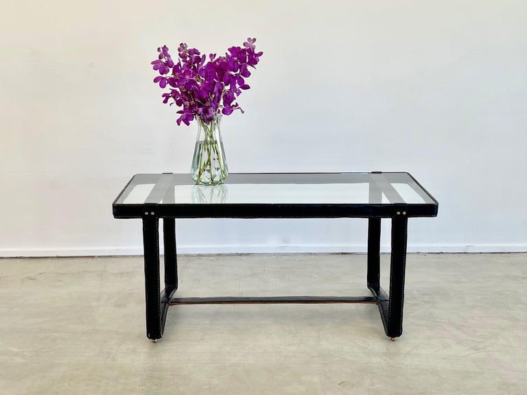 Jacques Adnet rectangular coffee table with signature leather stitching, curved base and brass detailing New glass top.