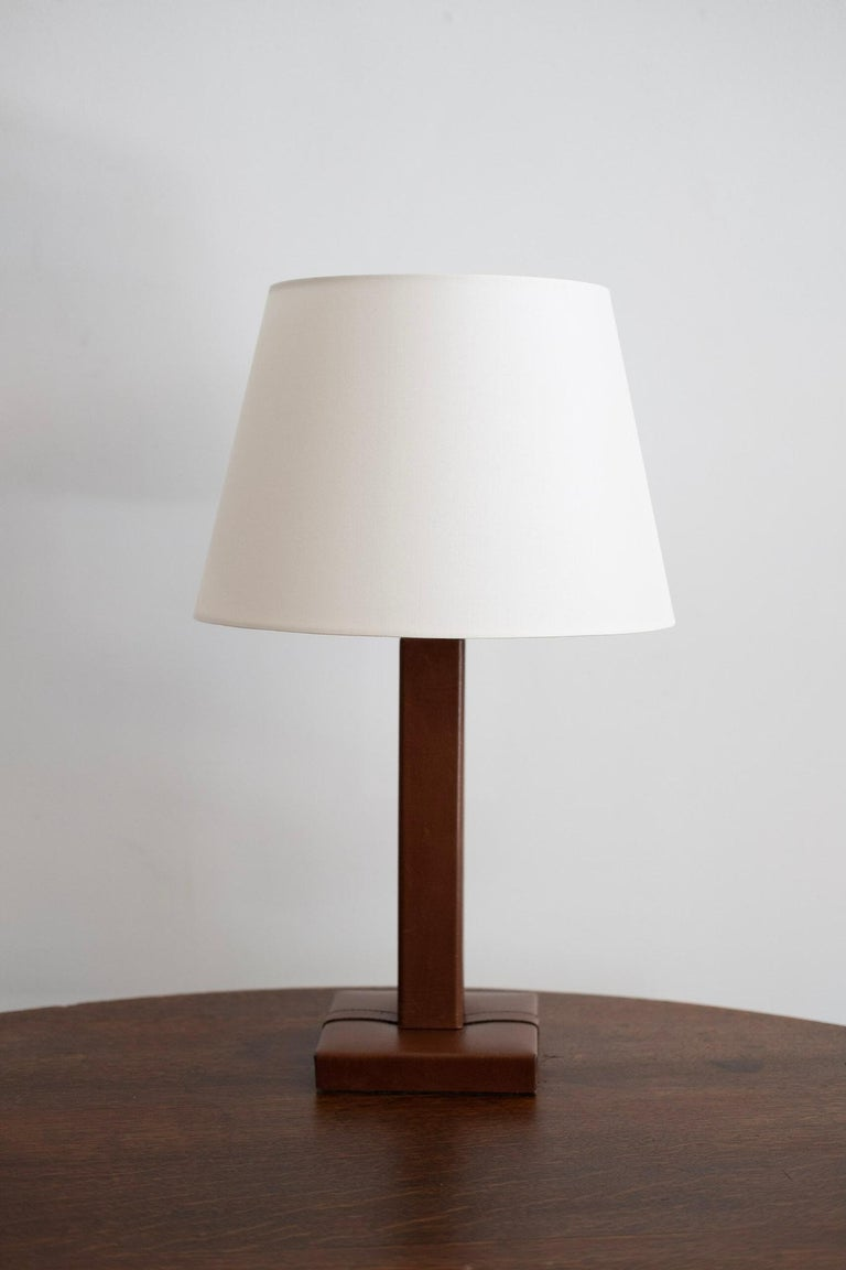 Jacques Adnet style table lamp. Aged brown leather with stitching. New shade and newly rewired.