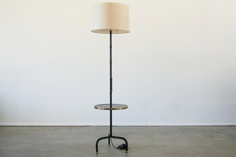 Jacques Adnet leather wrapped floor lamp with signature bamboo leather and brass stem with contrast stitching throughout. Floating table with trim accent.  Brass hardware and accents.  Rare find.  Newly rewired with new silk shade.