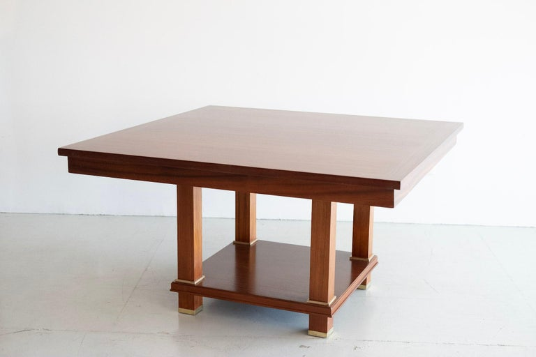 Important Jacques Adnet library table with thick square mahogany top with over flowing edge connected to four straight legs with bronze feet.