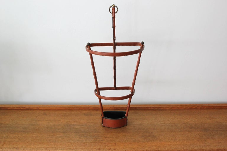 Handsome leather umbrella stand by Jacques Adnet. Saddle leather has signature Adnet contrast stitching and beautiful patina. Inset iron dish at the base to collect water. Excellent vintage condition. Very rare piece.