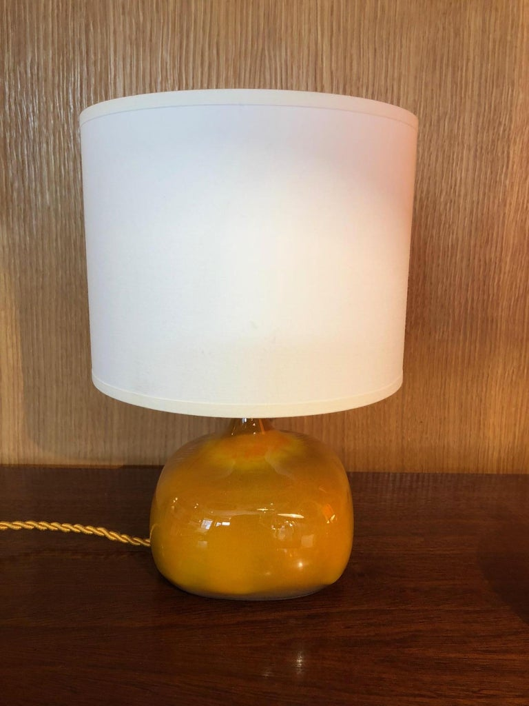 A lamp by the French ceramic artists Jacques and Dani Ruelland. A yellow orange glaze. Signed. Dimensions indicated below are without lampshade.