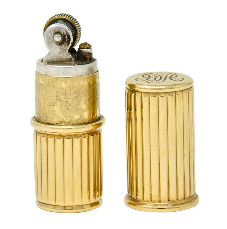 Designed as a sleek tubular form comprised of deeply ribbed polished gold  Cap slides off to reveal a lighter with functional flint wheel and remains of a wick  Numbered and fully signed Cartier London with monogrammed base  With maker's mark for