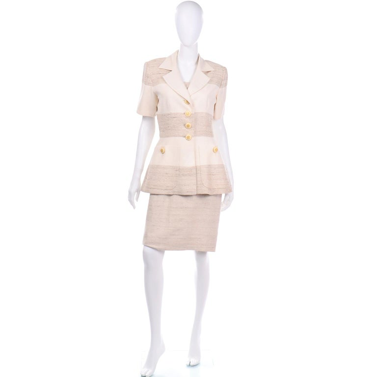 This is a beautifully made vintage Jacques Fath natural linen stripe short sleeve jacket with a sheath dress The sleeveless dress has a square neck and the waist is accentuated with darts, creating a flattering  silhouette. There is a back center