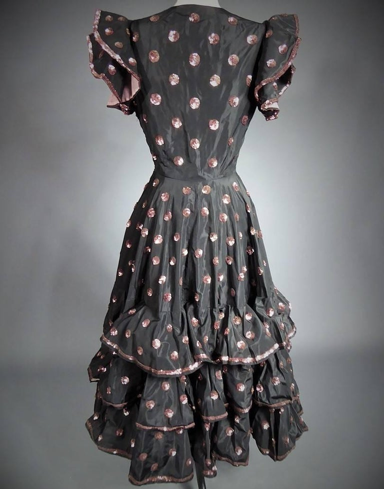 Circa 1950  France  Long dress in black silk faille with moiré effect by Jacques Heim. Embroidered with circles of iridescent metal pink sequins, edges bordered with sequins. Under skirt and sleeves in pink cotton tulle. Original metallic zipper.