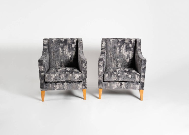 A work typical of the French midcentury, this pair of armchairs by the master Jacques Quinet exhibit identifiable elements of his style, the squared edges, gently tapered legs, and geometric sensibility.