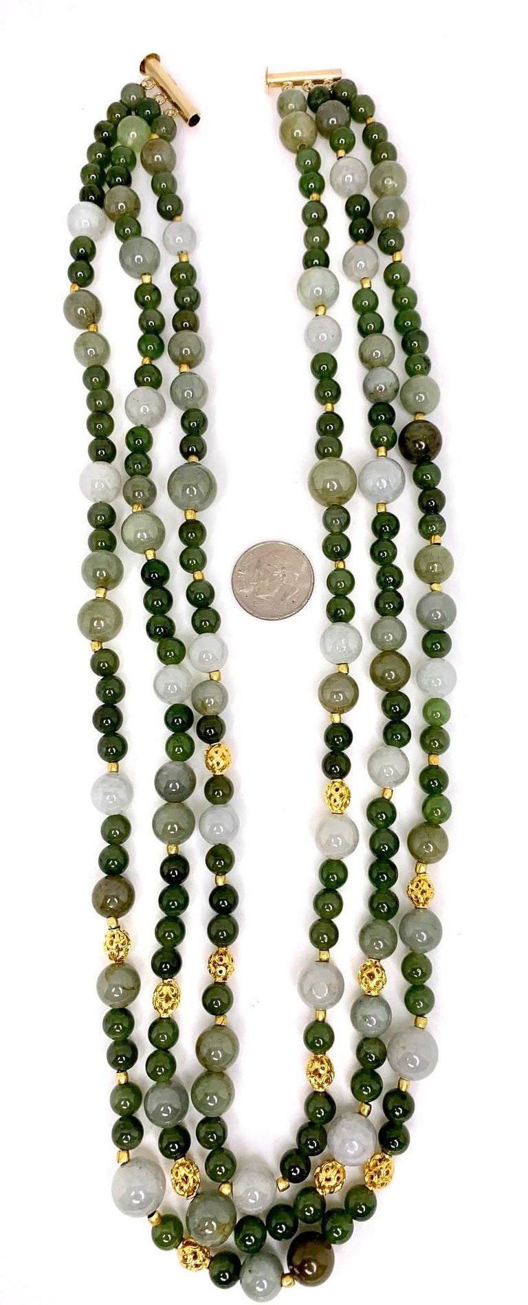 This impressive necklace features three strands of jade beads in varying shades of earth tones, green and silver. The beads have been hand-strung with 18k and 22k yellow gold beads and spacers. The shortest of the strands measures 17