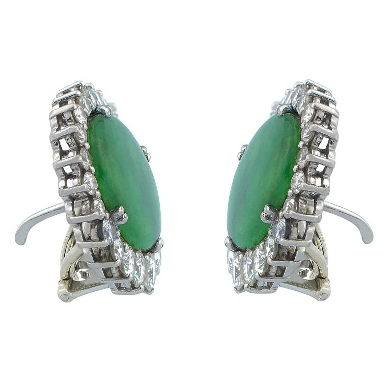 White gold earrings centered by oval jades surrounded by 38 round brilliant diamonds in increasing size set on three-prong mounts, totalling 2.74 carats in weight.