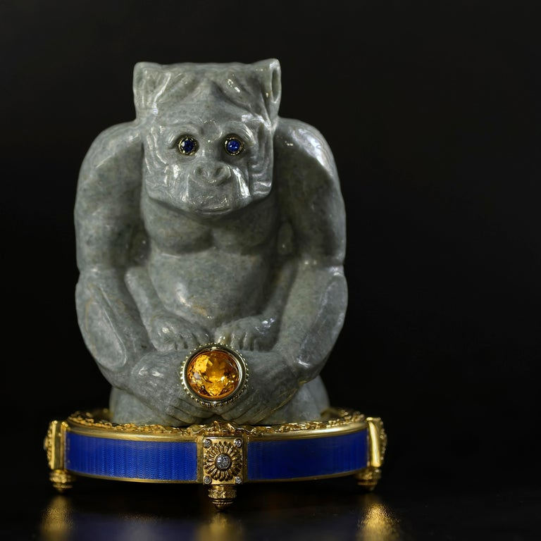 Jade monkey sculpture in Burmese jadeite, eyes set with gold and sapphires, paws holding a gold encased citrine. Pedestal in 24K plated sterling silver, set with diamonds, and covered with blue guilloche enamel.  A wise ape looks on with wonder and