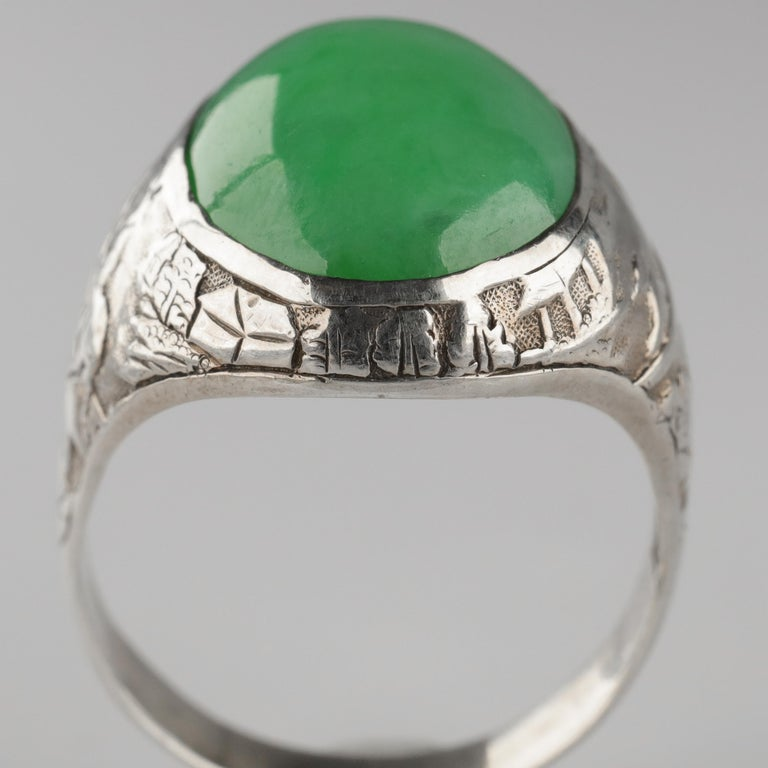 What a stunning work of art, this ring. The hand-carved shoulders of this circa 1910 Chinese silver ring depict on one side two figures in a sampan, a long, flat-bottomed wooden boat, and on the verso a figure riding a donkey. Structures and trees