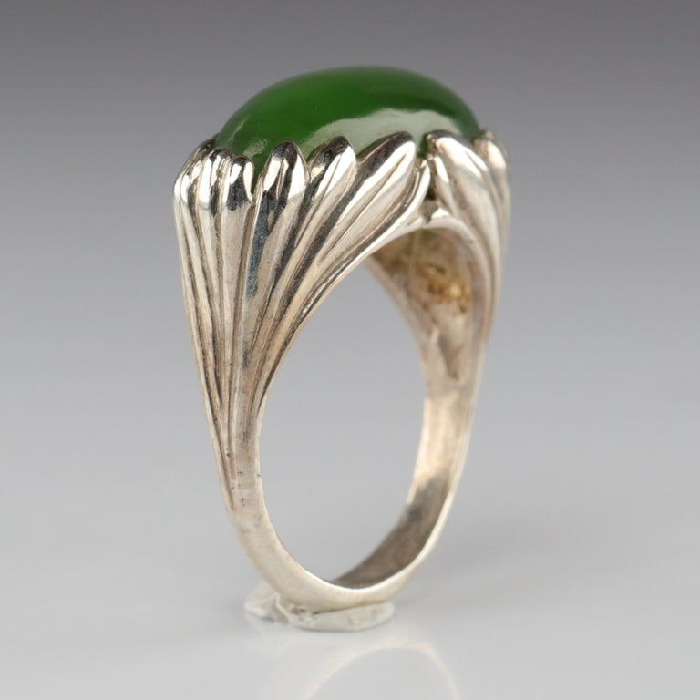 Not one but two artists created this ring. And it could be from the Art Nouveau era; the gorgeous symmetry of the carved silver clutching the summer-green jade cabochon, looking like something tucked beside a country stream. But this is not an