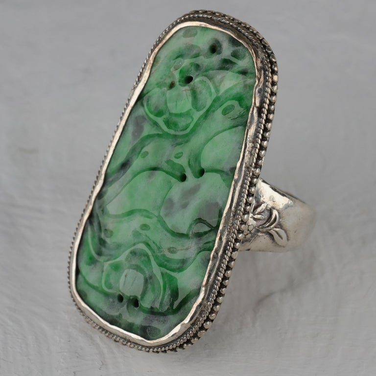A large (39 mm x 21 mm) and saturated mottled green natural and untreated jadeite jade plaque has been carved and pierced in a floral motif and set into a hand-fabricated silver mounting of exceptional artistry and craftsmanship. The jade carving