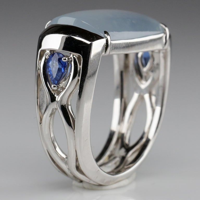 This is a one-of-a-kind hand-fabricated ring of untreated Burmese jadeite jade, royal blue sapphires and 18K white gold. An architectural scaffolding that bears a pair of opposing waveforms is set with two pear-shaped approximately .25 carat royal