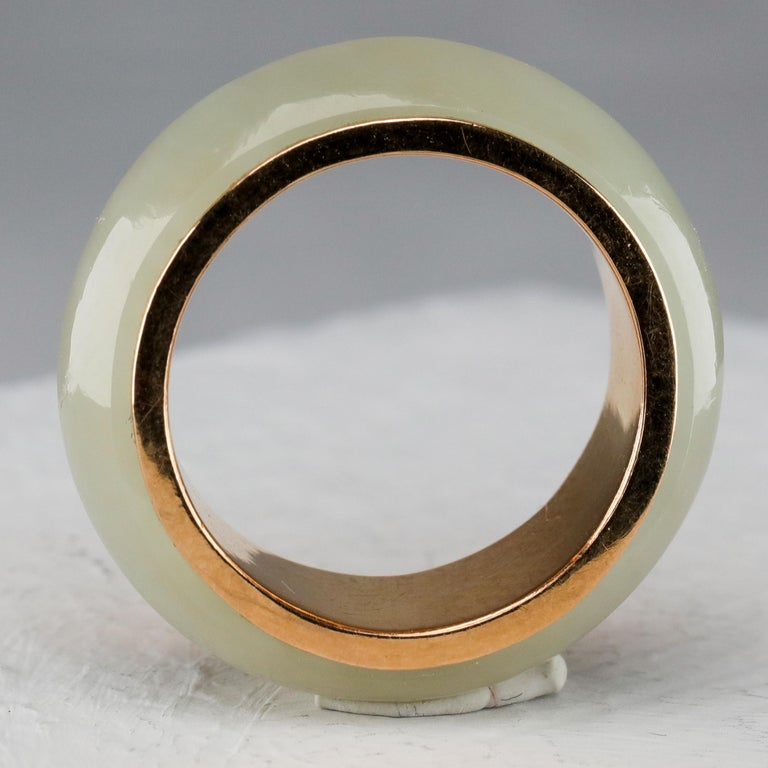 This is a high-quality jade and 14K yellow gold ring created in the 1970s. It features a hand-carved 100% natural and untreated (certified) nephrite jade ring in very pale green surrounding a solid 14K gold band. The jade has a luminous translucency