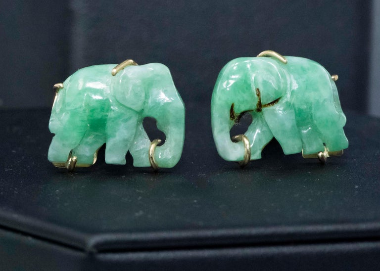 The present cufflinks are green jade elephant shaped cufflinks exhibiting good color throughout approximately 20mm wide tail to trunk by 15mm in height and are set in 14kt yellow gold mount with a depth of 32mm, circa 1960s. Additionally, they are