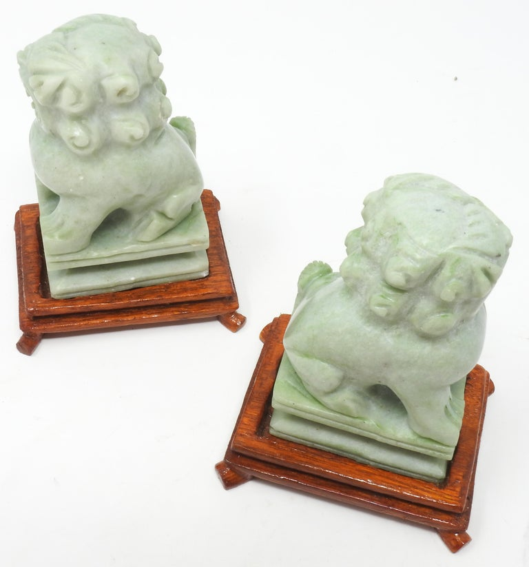 Offering this magnificent pair of Jadeite guardian foo dogs. They are a small simple pair done in the mid-20th century. The small wooden bases were hand carved. The foo dogs sit atop a plinth with simple lines and curves.