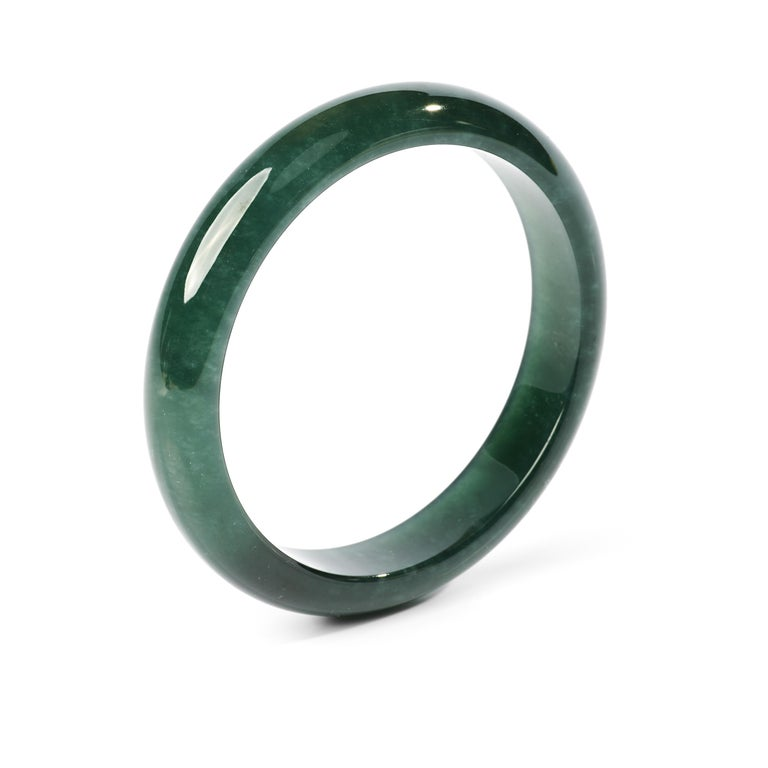 This bluish-green jadeite jade bangle is so translucent it looks like glass. It's the color of the ocean off the coast of Big Sur, California. If it fit me I would never take it off.   Carved to perfection, this gorgeous and rare bangle has an inner