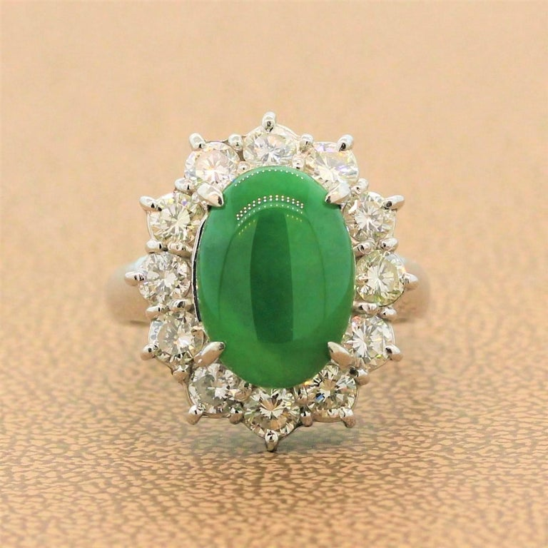 A marvelous ring featuring a GIA certified 4.77 carat jadeite jade with luscious green color and great luster. The oval cabochon jade is haloed by 1.50 carats of sparkling colorless round cut diamonds in a platinum setting.   Ring Size 6.75