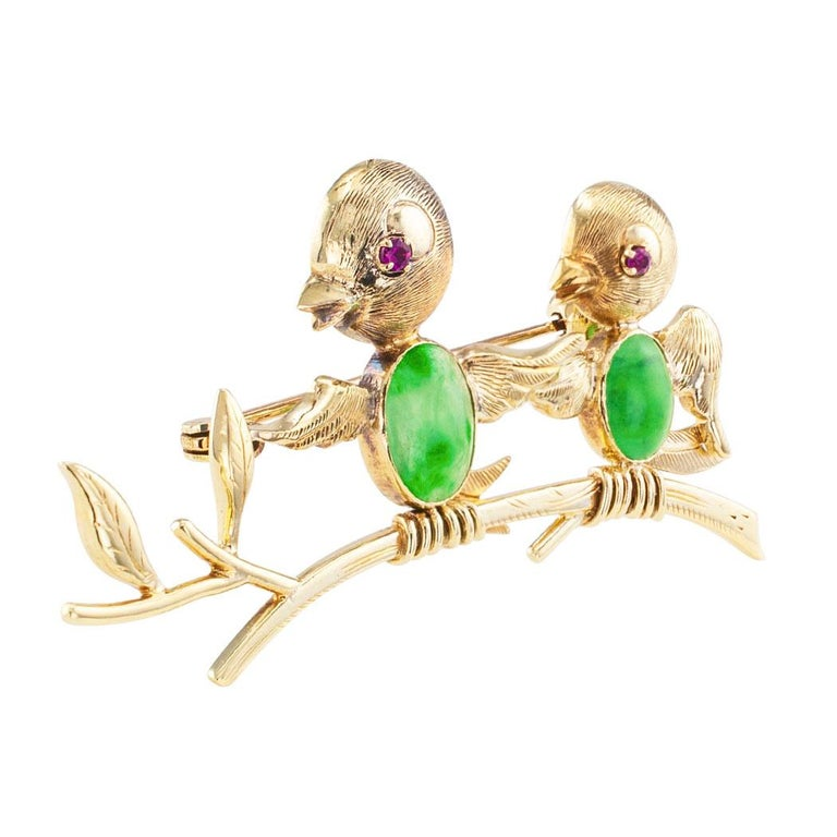 Jadeite ruby and gold bird brooch circa 1950. The design comprises two small birds perched on a single branch, the birds themselves have ruby-set eyes and jadeite breasts, crafted in 14-karat yellow gold. Very pristine condition consistent with age