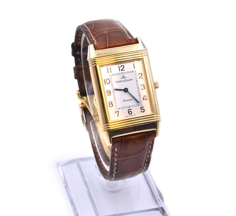 Movement: Manual Wind Function: hours, minutes Case: 23mm x 38mm yellow gold rectangular case, push/pull crown, sapphire crystal, reverso flip top case Dial: silver dial with blue steel hands, Arabic numerals Band: brown leather strap with
