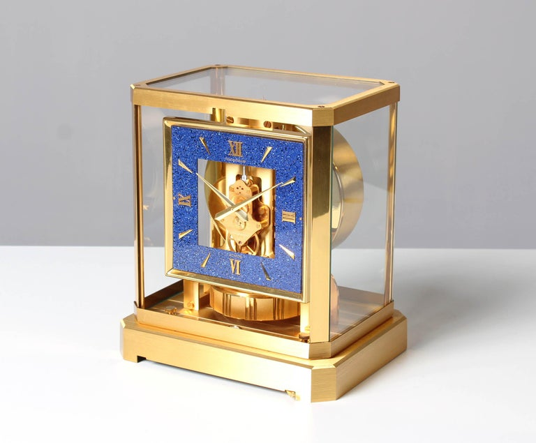Switzerland Brass gold plated Year of manufacture 1979  Dimensions: H x W x D: 23 x 21 x 16 cm  Description: Atmos VIII in matte brushed gold plated case with polished stands. Rotating pendulum with vertical milled stripes. Square dial in
