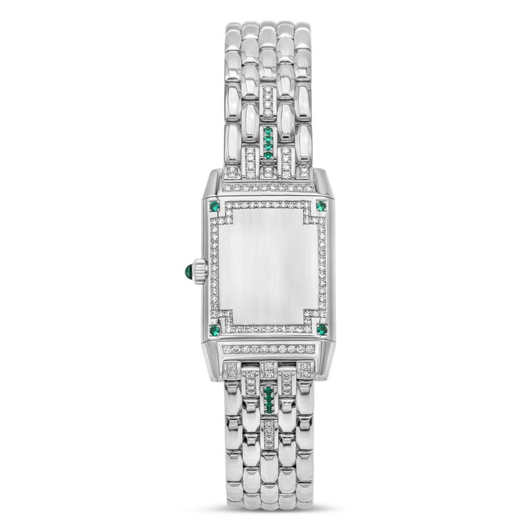 A rare and iconic Jaeger-LeCoultre Reverso.  The case features a white dial set with diamonds to mark the numbers with dauphine hour and minute hands. White gold bezel encrusted with diamonds and emeralds. Case reverses to a plain diamond encrusted