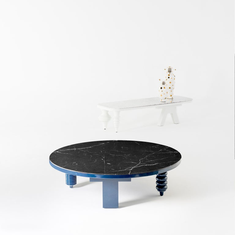 MDF base and legs in turned solid alder wood, lacquered in blue gloss  Marble table tops in Carrara Venato or Nero Marquina.  Rounded table measures: Ø 80/120x H.35 cm.