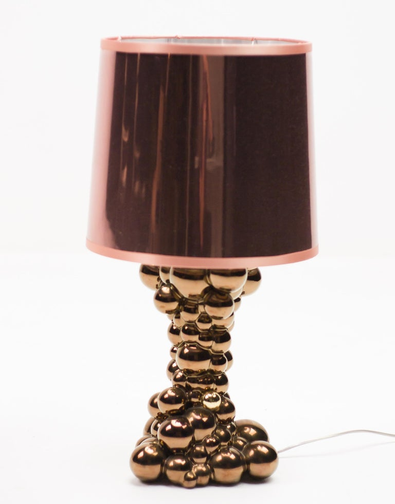 Bubbles table lamp in glossy copper ceramic designed by Jaime Hayon for Bosa.  The bubbles lamp evokes the effervescent effect of a flurry of bubbles. The material that is transformed by a touch and a body that fills with light. To achieve the